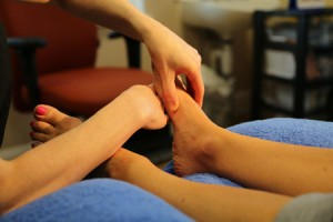 Hands working on feet for reflexology